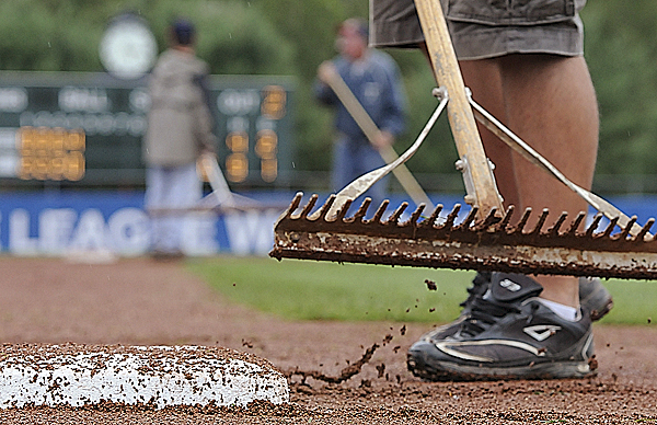 The field maintenance crew was out in force Tuesday trying to keep the Mansfield Stadium baseball field playable as showers fell throughout most of the day. By late afternoon, the crew had applied three tons of Turface, a clay-based soil conditioner, to help dry the infield.