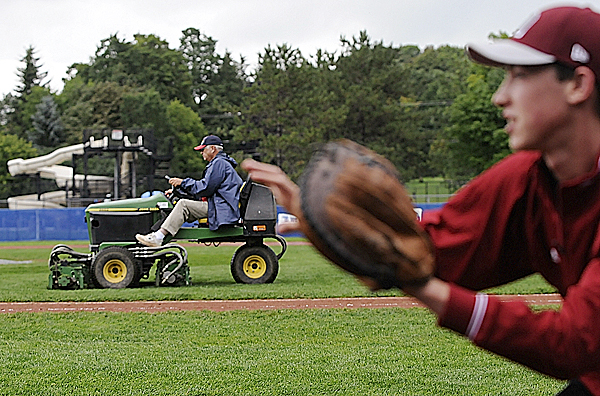 BDN Photo by John Clarke Russ Ron St. Pierre, field manager at Mansfield Stadium in Bangor, mows the infield late Tuesday afternoon as Jeremy Bissell of Maine District 3 representative Brewer/Orrington gets in some practice during the lengthy rain delays. Two Senior League World Series games were played, but two others had to be postponed to Wednesday and Thursday.