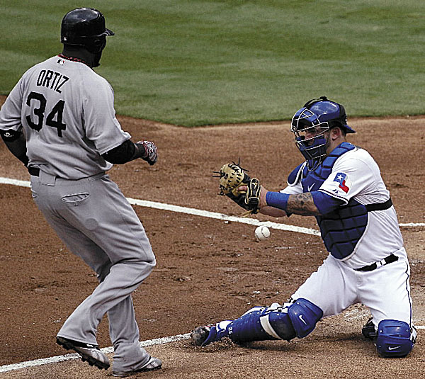 Boston Red Sox designated hitter David Ortiz scores on a double by Carl Crawford as Texas Rangers catcher Mike Napoli is unable to hang onto the throw in the first inning of Wednesday night's game in Arlington, Texas. Boston won 13-2.