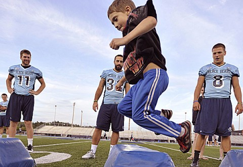Trey Lyon of Bangor jumps through an obstacle course Wednesday during a Meet the Black Bears event at the University of Maine in Orono. Black Bear football players John Ebeling (left), Troy Eastman (center) and Warren Smith look on.