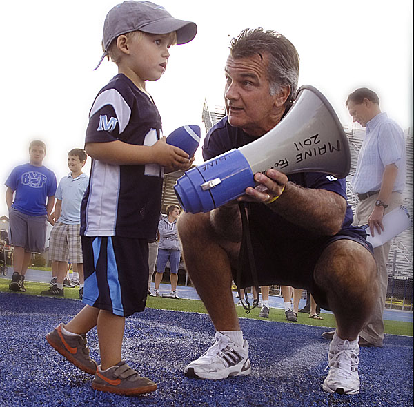 University of Maine head football coach Jack Cosgrove offers the use of the bullhorn to Patrick Cahill of Bangor to help get things started Wednesday evening during a Meet the Black Bears event at Alfond Stadium in Orono. Cahill is the son of UMaine assistant coach Kevin Cahill.