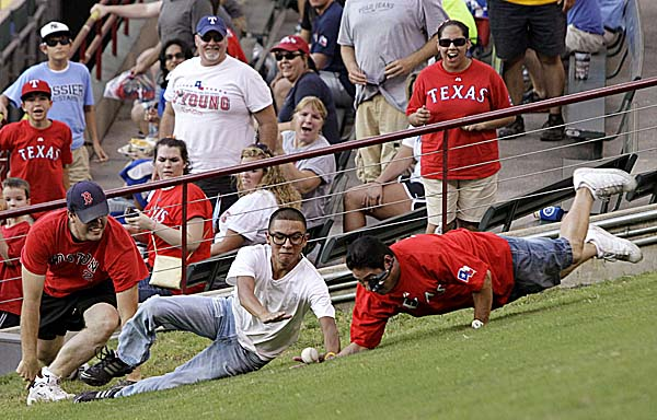 Baseball fans scramble and dive for a home run ball hit to center field by Boston Red Sox's Adrian Gonzalez off a pitch from Texas Rangers' Alexi Ogando in the first inning Thursday night, Aug. 25, 2011, in Arlington, Texas.