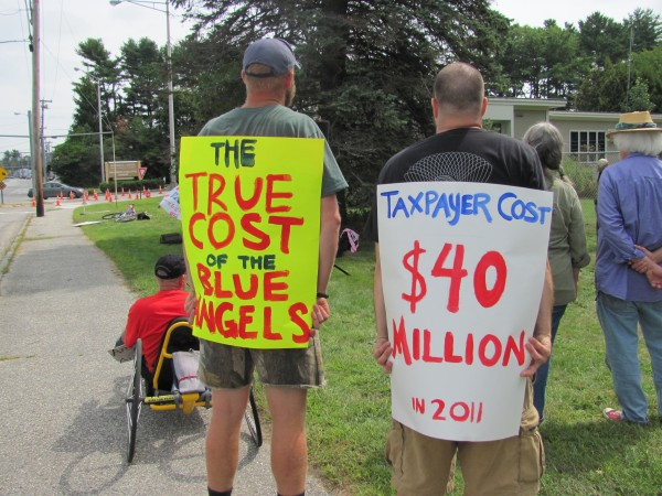 Two protesters outside the Great State of Maine Air Show and Business Aviation Expo in Brunswick display their signs to motorists while listening to a presenter who was part of the protest on Saturday, August 27, 2011.