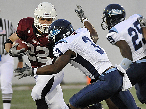 UMass' Jonathan Hernandez is tackled  by Maine's Trevor Coston during a  Colonial Athletic Association game last season. The CAA will be losing two New England teams in the next two years as UMass is moving up to the FBS (formerly known as Division I-A) after this season and, following the 2012 season, the University of Rhode Island will drop to a league with a lower number of scholarships.