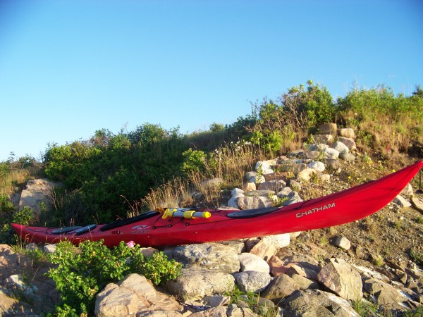 Levi Bridges' touring kayak safely stored above the high-tide line. Slippery rocks exposed at low tide provide a formidable obstacle for kayakers seeking to bring all of their belongings safely up onshore.