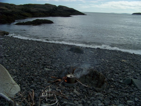 A small cook fire (like the one pictured above) should be made well below the high-tide line, with no wood from the mainland island. A metal cooking pan (above) allows campers to neatly dispose of hot ashes in the water and mitigate the potential spread of fire.