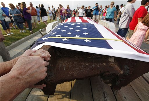 People touch a steel beam from the World Trade Center, shown during its arrival from New York City in Wauseon, Ohio, in June 2011. The 12-foot beam, salvaged from the Twin Towers' rubble, was escorted in a procession of emergency vehicles from New York City to Wauseon where it will be on display until a permanent memorial to the Sept. 11, 2001, terrorist attacks is erected at the Fulton County Fairgrounds.