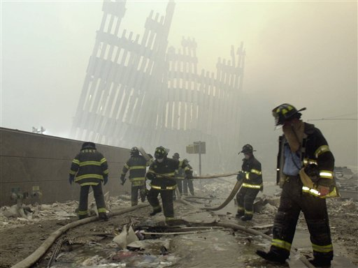 With the skeleton of the World Trade Center twin towers in the background, New York City firefighters work amid debris on after the Sept. 11, 2001 terrorist attacks.