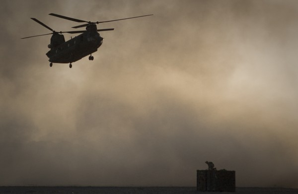 A U.S. Marine tries to take cover, perched on a container, trying to shelter from the dust as a Chinook helicopter arrives to pick up supplies at Forward Operating Base Edi in the Helmand Province of southern Afghanistan, in this June 9, 2011 file photo. Afghan President Hamid Karzai says 31 U.S. special forces and seven Afghan soldiers were killed when a helicopter, similar to the one shown crashed in eastern Wardak province Saturday Aug. 6, 2011.