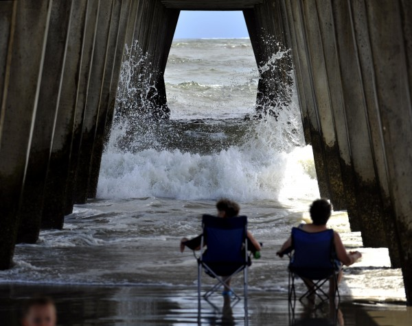Visitors from Dahlonega, Ga., watch the surf crash into the pylons under the pier on Tybee Island, Ga., Wednesday, Aug. 24, 2011, as Hurricane Irene heads toward South Florida. Forecasters are predicting that Irene will strike North Carolina's Outer Banks on Saturday.