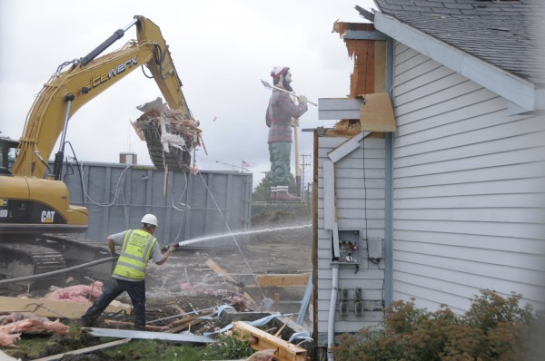A worker with Hermon-based Sitewerx, an excavation, demolition, landscaping and site preparation company, sprays water to control dust as a co-worker uses an excavator to remove debris while razing the Bangor Chamber of Commerce building Monday morning. The demolition is part of the site work for the future Bangor Arena.