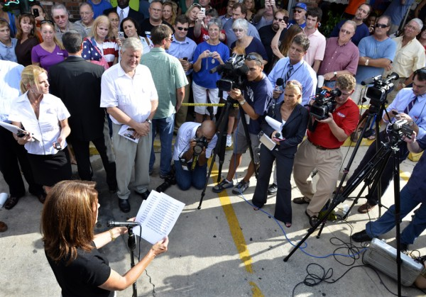 Republican presidential candidate Rep. Michele Bachmann R-Minn. (bottom left) reads a prepared statement to the media gathered during a campaign stop at Angie's Subs in Jacksonville Beach, Fla. Friday, August 26, 2011.