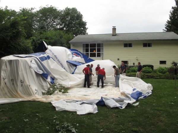 Crews take apart a blimp that broke free of its moorings at an airport and landed in a resident's backyard on Sunday, Aug. 14, 2011, in Worthington, Ohio.