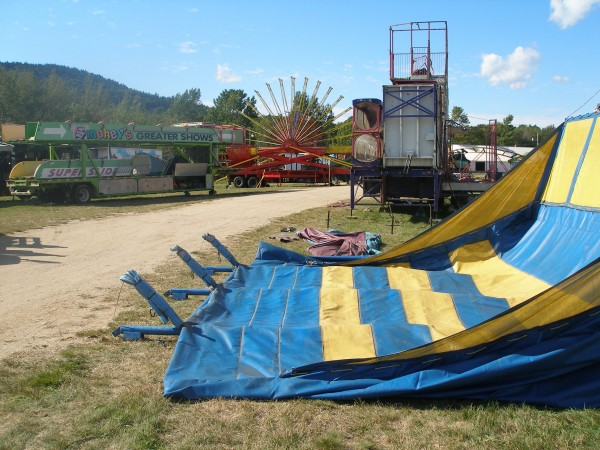 Tents, vendor stands and carnival rides wait to be erected on