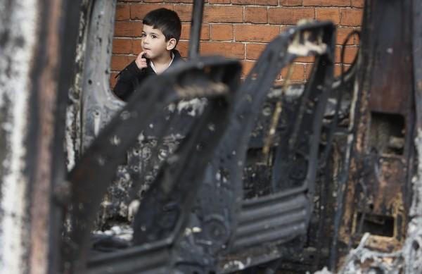 An unidentified boy reacts behind a burned car in Tottenham, north London, on Sunday, Aug. 7, 2011, after a demonstration against the death of a local man turned violent and cars and shops were set ablaze.