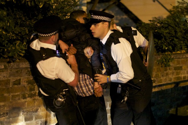 A youth is arrested for a public order offense by British police officers following skirmishes with police in Camden Town, north London, early Tuesday, Aug. 9, 2011. Violence and looting flared across London on Tuesday, and spread to a second major city, as shops and cars were set ablaze and authorities struggled to contain a third night of unrest in Britain's capital, which will host next summer's Olympic Games.