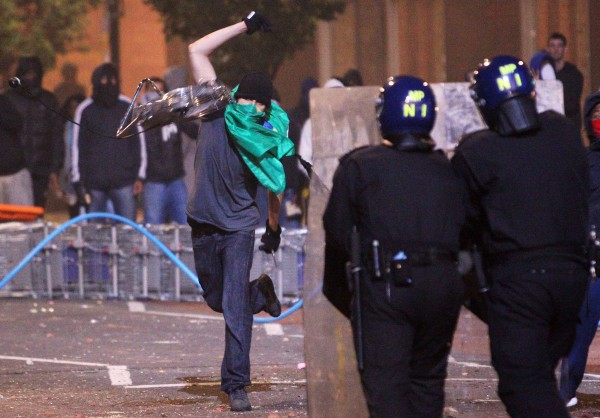 A masked protester hurls an object toward riot police officers in Tottenham, north London, on Sunday Aug. 7, 2011. The gritty north London neighborhood of Tottenham exploded in anger Saturday night after a young man was shot to death by police.