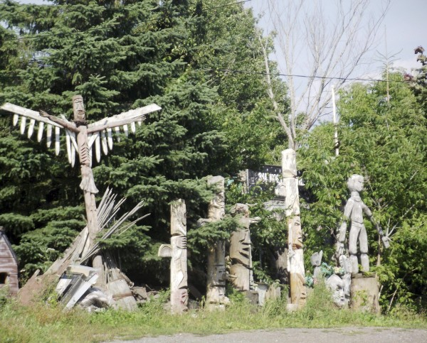 "Totem poles and other art work stand outside of the entrance to the property at 314 Military St. owned by Jerry Cardone, a Houlton artist, on Aug. 18, 2011. Aroostook County Superior Court Justice E. Allen Hunter ruled on Nov. 15, 2010, that the property constituted an automobile graveyard and a junkyard under state statute and was a ""public nuisance"" under Houlton code. The site had become so cluttered that Cardone could no longer drive his truck onto the property, and Hunter could not walk unimpeded through the yard when he visited it last summer before making his ruling. The cleanup effort cost $56,027 and 427 hours of work."