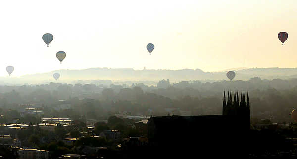 Hot air balloons drift off into a foggy morning above St. Peters and Paul Basilica in Lewiston on Friday morning after the first launch of the Great Falls Balloon Festival.