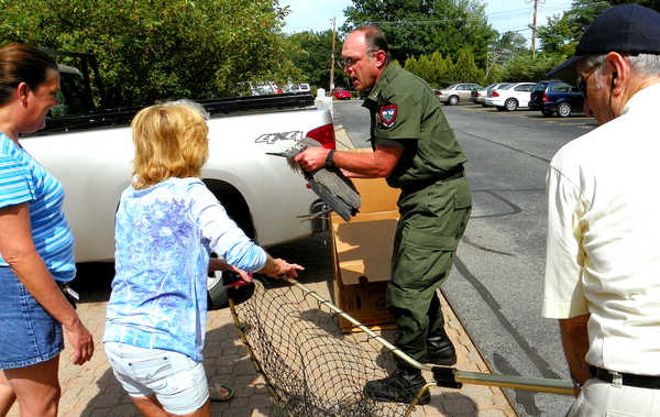 Residents of Barker Mill Arms in Auburn help Game Warden Rick Stone rescue an injured great blue heron from the Little Androscoggin River on Wednesday afternoon.  The residents called Stone after noticing the creature's wing was apparently injured.