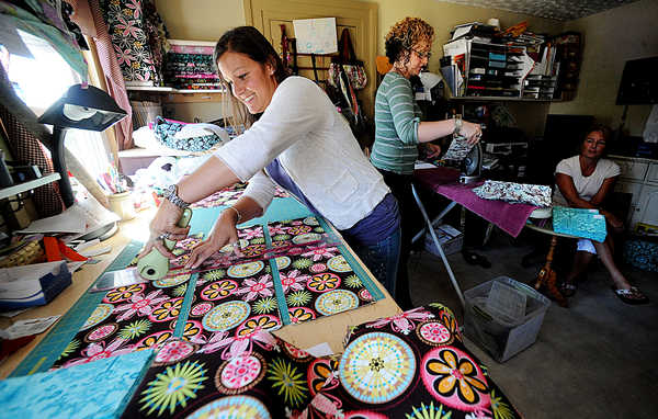 Sarah Dube Legare, left, cuts fabric for the 800 notepad holders she is hand-making for the Emmys' official gift bags at her Lewiston home Tuesday. Because of the large number needed and the short deadline, Legare has enlisted the help of friends, including Cari Beach, center, of Auburn and Nicki Therrien of Greene.