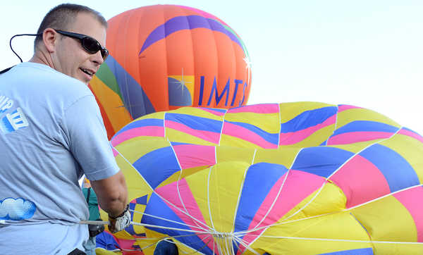 Steve Boucher holds the crown line of his father Andre's balloon Passion just before an accident Saturday night at the Great Falls Balloon Festival in Simard-Payne Memorial Park in Lewiston. Several people were taken to the hospital after being burned.