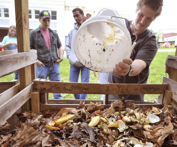 Bangor High School student Mike Mixon dumps waste into a compost bin in June. The composted soil is used to grow vegetables in the school's garden. With him are (from left) Tiffany Strout, Nick Dumond and Shane Rinks.