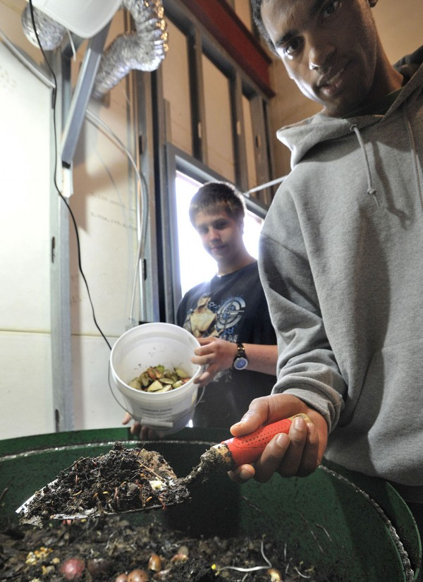 Bangor High School students Michael Mixon (left) and Shane Rinks show the results of what leftover scraps and hungry worms can produce to the tune of one ton per year in June. The composted soil is then used to grow vegetables in the school's garden.