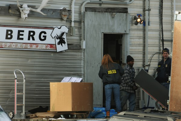Federal agents watch as filing cabinets are loaded into a moving truck at Berg Sportswear in Corinna in January 2011.