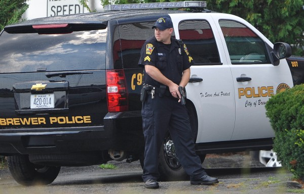 With gun drawn, Brewer Police Cpl. Nelson Feero, helps secure the perimeter of the Cozy Inn in Brewer as fellow officers with his department and the Penobscot County Sheriffs Department made an arrest there Friday afternoon, Aug. 19, 2011.