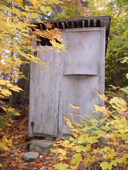 This is a Yogi outhouse. When you come to the great north woods of Maine for retreat and sanctuary, our outhouse comes complete with Tibetan prayer flags over the hole. Let the chi flow as you leave your offering to the Gods.