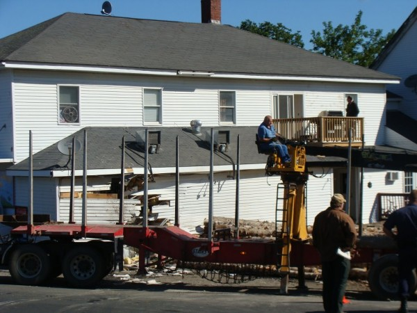 Workers remove logs that spilled early Tuesday, Aug. 23, 2011, when the driver of a tractor-trailer truck lost control of his vehicle while rounding a curve in Cambridge.
