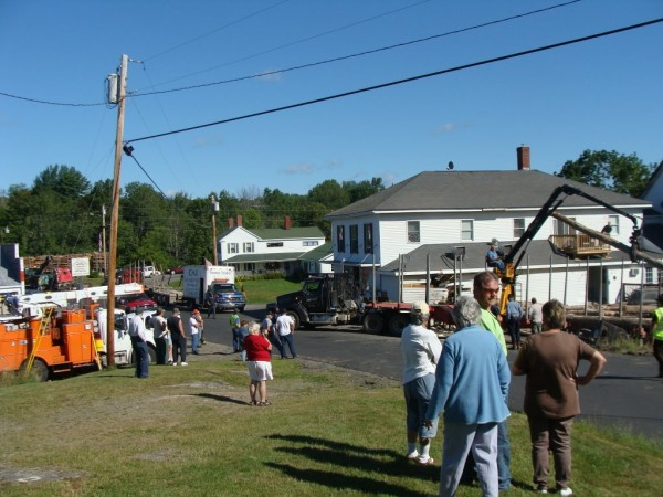 Several Cambridge residents watched Tuesday, Aug. 23, 2011, as logs that were lost during an early morning accident were reloaded onto a flatbed.