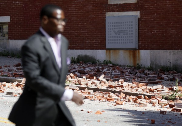 A man walks past bricks that fell off a house once owned by the late Rep. Parren Mitchell, D-Md., after an earthquake was felt in Baltimore, Tuesday, Aug. 23, 2011. One of the strongest earthquakes ever recorded on the East Coast shook buildings and rattled nerves from South Carolina to New England on Tuesday and forced the evacuations of parts of the Capitol, White House and Pentagon.