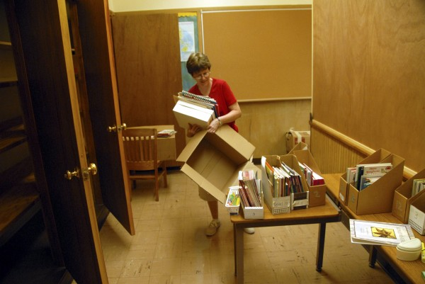 Title 1 teacher Gail Rucci unpacks boxes of books as she and other teachers and volunteers help move Opal Myrick School into Schenck High School of East Millinocket on Monday, Aug. 8, 2011.