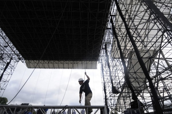 Mike Fischer, chief of operations for Old Town-based Production Services of Maine, helps rig stage lighting before it was hoisted to the roof of the Railroad Stage during Thursday's preparations for the American Folk Festival on the Bangor Waterfront. The festival kicks off Friday evening and runs through late Sunday afternoon.
