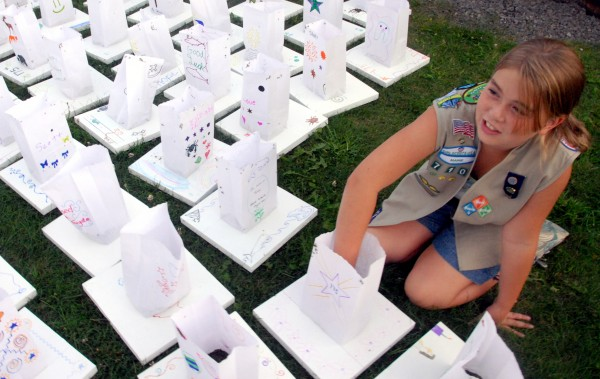 "Nine-year-old Girl Scout Brianna Cobb of Greenville adds dirt to a floating ""lantern"" made of paper and polystyrene in Greenville at Moosehead Lake during her town's celebration of its 175th birthday on Saturday, Aug. 28, 2011."
