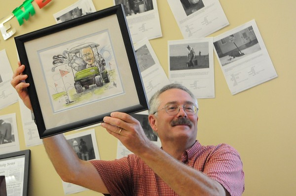Long-time Bangor Daily News photographer and photo editor Scott Haskell proudly holds up a caricature of himself that BDN cartoonist George Danby presented him during his Haskell's retirement party Friday.