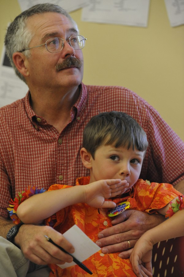 As he holds his 5-year-old son, Jackson Haskell, long-time Bangor Daily News photographer and photography editor Scott Haskell listens to praise from colleagues during his retirement party Friday.
