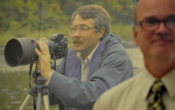 An early 1990s action photo of Scott Haskell hung behind BDN editor-in-chief Mike Dowd, right, as Dowd and other colleages lauded the long-time Bangor Daily News photographer and photography editor at Haskell's retirement party at the newspaper Friday.
