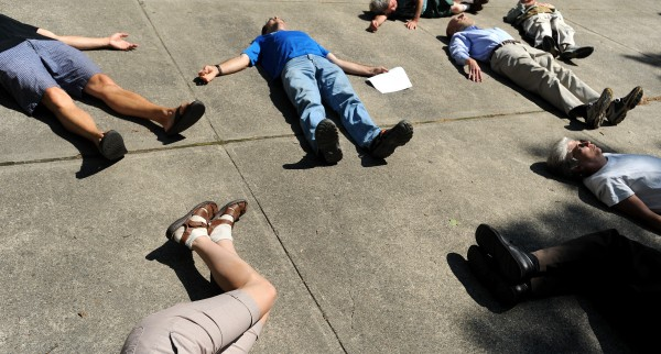 People lay down on the ground during a commemoration ceremony in Bangor remembering the victimes of the atomic bombs dropped on Hiroshima and Nagasaki 66 years ago. The Peace & Justice Center of Eastern Maine organized the event that remembered victims of the only nuclear weapons that were used against people. The ceremony on Saturday, Aug. 6, 2011, included a description of the explosions and was followed by a description of nonviolent action taken by people in Washington state at a nuclear warhead depot.