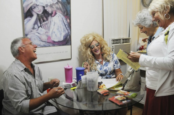 This Friday, Aug. 5, 2011 photo shows Kevin Farrell's partner Geoffrey Michael, left, Kevin Farrell dressed as Dee W. Ieye, second from left, and clients Barbara Cassidy, right, and Susanne Cameron as they share a laugh after Cassidy and Cameron placed an order for Tupperware products from Farrell at a Tupperware party in Bellflower, Calif.