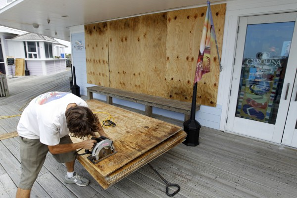 Jeremy Pickett cut pieces of boards to protect the windows in a shopping store in Cape Hatteras in preparation for Hurricane Irene at Cape Hatteras, N.C., on Wednesday, Aug. 24, 2011. Evacuations began on Ocracoke Island off North Carolina as Hurricane Irene strengthened to a major Category 3 storm over the Bahamas on Wednesday with the East Coast in its sights.