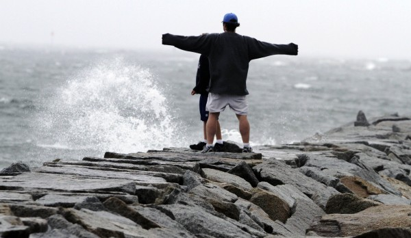 Waves crash across the jetty as Alex Brown of Saco and his son watch the storm in Saco as Tropical Strom Irene makes its way into the state on Sunday, Aug. 28, 2011. Irene caused more than 4.5 million homes and businesses along the East Coast to reportedly lose power over the weekend, and at least 11 deaths were blamed on the storm.