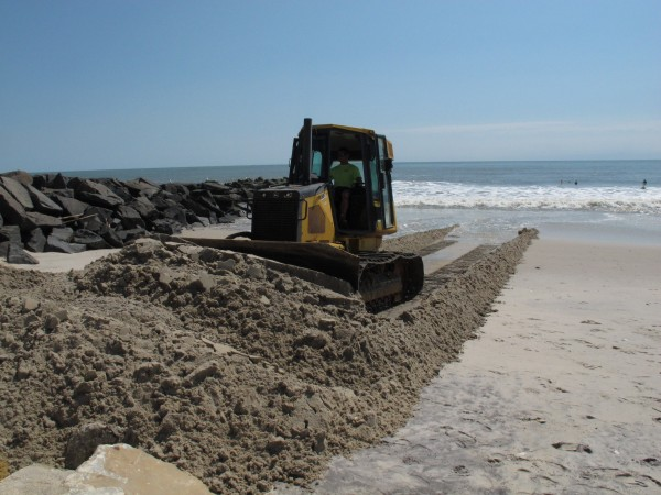 A worker uses a bulldozer to push sand away from the ocean toward badly eroded dunes in the Holgate section of Long Beach Township, N.J., Monday Aug. 29, 2011.