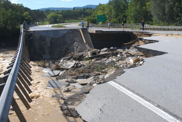 People take photos of a washed-out section of Route 7 south of Rutland, Vt., Monday, Aug. 29, 2011, after heavy rains from Tropical Storm Irene that swelled rivers the day before.