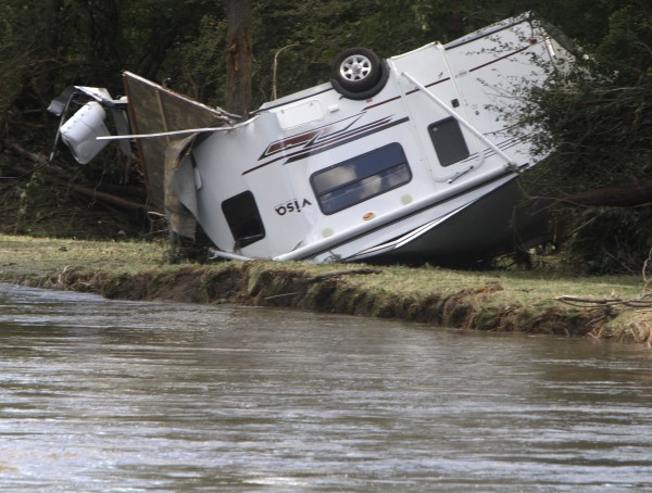 A recreational trailer lies upside down on a riverbank in Berlin, Vt., Monday, Aug. 29, 2011, after it was washed away by flash flooding caused by heavy rains from Tropical Storm Irene.