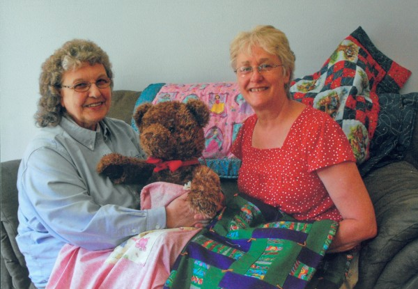 "Eda Stoll (right) and Linda Applebee with quilts and teddy bear, which are included in the ""Bags of Love"" given to children who are removed from their homes by social service agencies for their own protection."