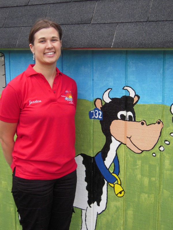 Jessica Blackstone beside one of the five small barns that house Lil' Farmers at The Fair exhibits at the Northern Maine Fair in Presque Isle.