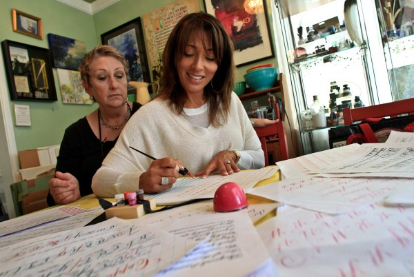 DeAnn Singh, seen teaching calligraphy to Eileen Ludwick, is the foremost calligrapher in Southern California. She's received a number of movie commissions, just received some new work from Barbra Streisand, and with some 30 years experience, she has taught beautiful writing - which is what calligraphy means - to students in the area.
